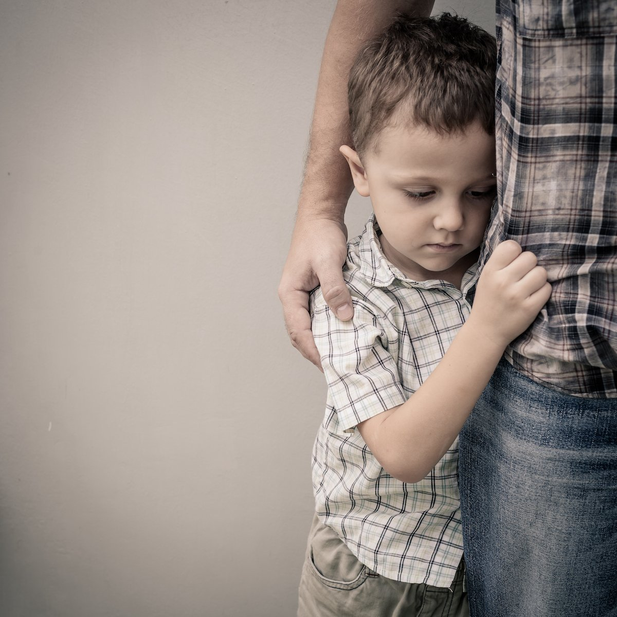 Anxious boy holding on to father.